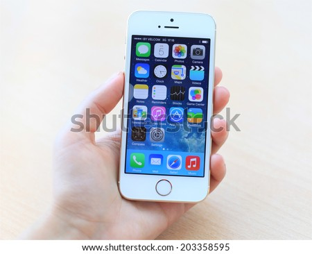 MINSK, BELARUS - JULY 05, 2014: Woman holding brand new white Apple iPhone 5S. Social media are trending and both business as consumer are using it for information sharing and networking.  - stock photo
