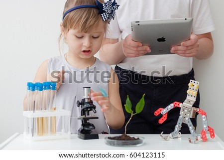 Minsk, Belarus - March 19, 2017: 3 years old little girl and teenager boy are behind the desk. Microscope and the tree are near her. E-learning. Stem education. Modern education. iPad apple.