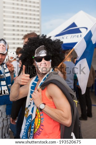 MINSK, BELARUS - May 18, 2014: ICE HOCKEY WORLD CHAMPIONSHIP, MINSK-ARENA, The hockey fan from Finland with national flag in mask and black wig - stock photo