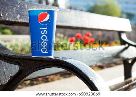 Minsk, Belarus, may 19, 2017: paper cup of Pepsi on a bench in the city on a blurry background of red flowers in the color of the logo Pepsi. Pepsi is a carbonated soft drink produced PepsiCo.