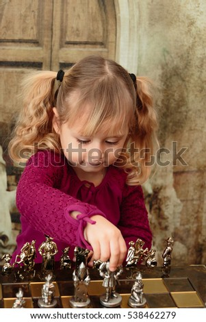 Minsk, Belarus - November 2016: A child playing chess metal handmade. Beautiful and unusual chess pieces. Children's portrait. Children's emotions.