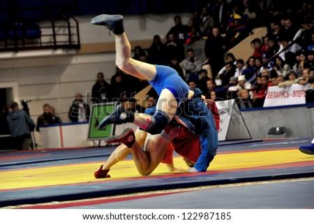 MINSK, BELARUS - NOVEMBER 10: Unidentified sportsman (red) throws his opponent during SAMBO (Wrestling) WORLDCh-2012 on November 10, 2012 in Minsk, Belarus. - stock photo