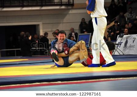 MINSK, BELARUS - NOVEMBER 10: Unidentified wrestler (red) locking his opponent's arm during SAMBO (Wrestling) WORLDCh-2012 on November 10, 2012 in Minsk, Belarus. - stock photo