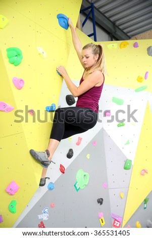 MINSK, BELARUS - SEPTEMBER 16, 2016: A young female testing new indoor climbing wall
