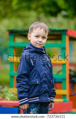 Minsk, Belarus - 1 September, 2017: portrait of a small preschool boy on the outdoors in front of a playground background