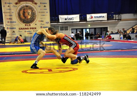 MINSK, BELARUS - SEPTEMBER 16: Unidentified female (red) scores a three point throw during Grand Prix for the prizes A.Medved in freestyle wrestling on September 16, 2012 in Minsk, Belarus. - stock photo