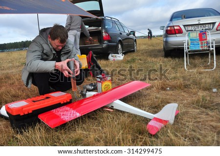 """MINSK, BELARUS â?? SEPTEMBER 5 Unidentified male fills-up airplane on the """"USSR Cup 2015"""" (Competition racing radio-controlled model classes F3D and Q500) on September 5, 2015 in Minsk, Belarus. - stock photo"""