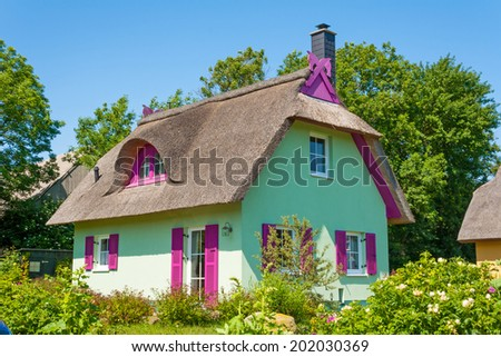 mint green thatched-roof vacation home with garden - stock photo