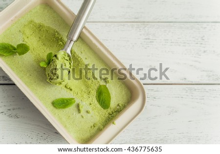 Mint ice cream in a container on wooden background - stock photo