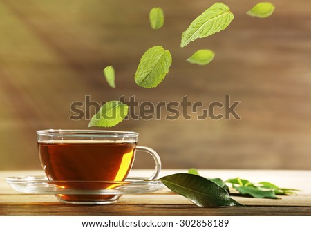 Mint leaves falling in cup of green tea on wooden background - stock photo