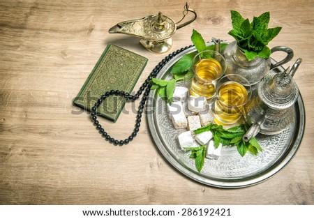 Mint tea, delight, arabian lantern, holy book quran and rosary. Islamic holidays decoration. Ramadan kareem. Vintage style toned photo - stock photo