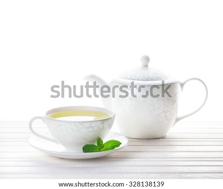 Mint tea in the cup near teapot at white background   - stock photo