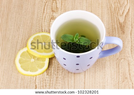 Mint tea with mint leaf and lemon on wooden background