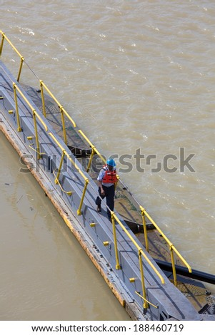 MIRAFLORES LOCKS, PANAMA, JANUARY 03: Unidentified worker crossing the canal of Panama at Miraflores. On January 03 2014 in Panama City. - stock photo