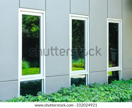 miror windows in the brick  wall with a reflection of the fores - stock photo