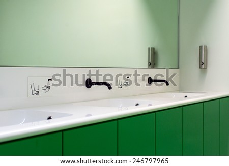 Mirror and faucet in public bathroom. - stock photo