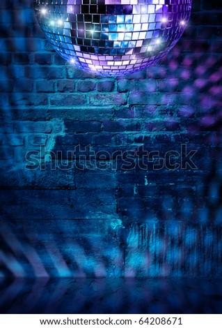 Mirror ball lights on dramatic dark disco brick wall - stock photo