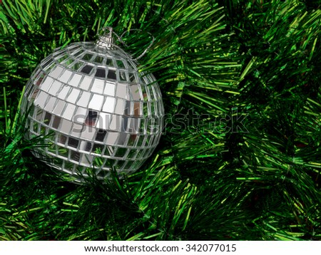 MIrror ball style Christmas bauble on bed of cheery green tinsel. Festive background. - stock photo