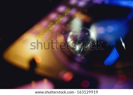 Mirror disco ball reflected in DJ's turntable. Tilt shift lens used to accent the globe and sublime toned filter applied for more natural effect - stock photo