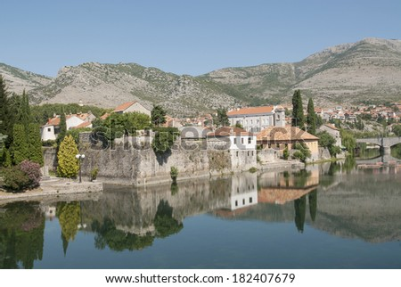 Mirror image of the old buildings in the town of Trebinje, Bosnia and Herzegovina in the water of the river, landscape photo - stock photo