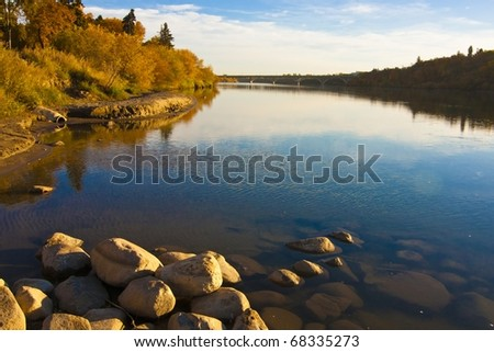 Mirror image reflections in the river during autumn - stock photo