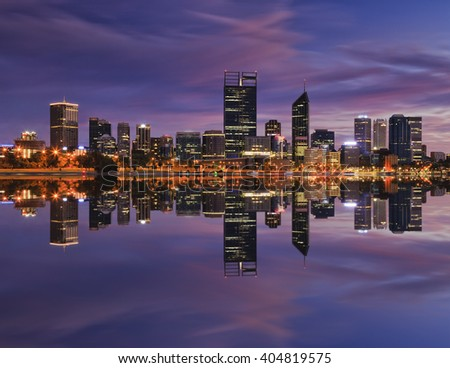 Mirror like reflection of Perth city CBD towers and skyscrapers in still waters of Swan river at sunrise with pink clouds in blue sky.