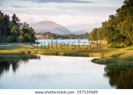 Mirror like reflections upon Loch Insh near Kincraig in the Cairngorms National Park, Scotland, UK - stock photo