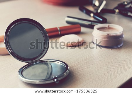 Mirror, powder, puff, mascara, eyeliner and other cosmetics on the table - stock photo