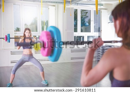 Mirror reflection of a fitness instructor with barbell - stock photo