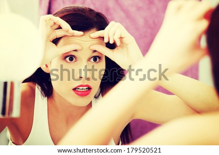 Mirror reflection of a woman worrying because of wrinkles on her forehead. - stock photo