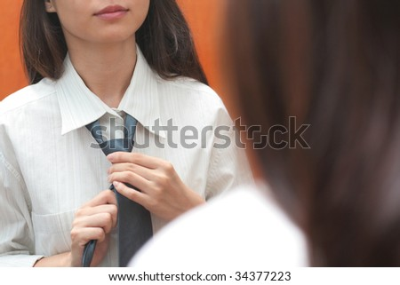 Mirror reflection of a young career lady adjusting her necktie - stock photo