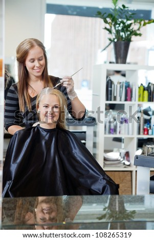 Mirror reflection of beautician applying color dye to woman's hair at parlor - stock photo
