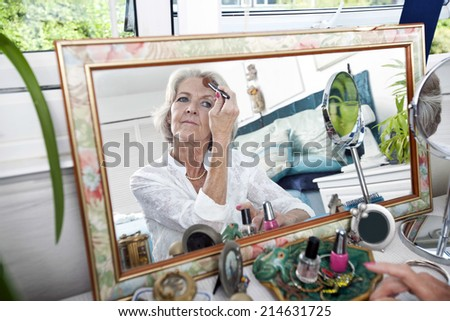 Mirror reflection of senior woman applying blusher at home - stock photo