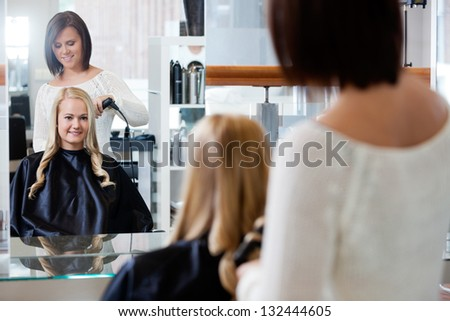 Mirror reflection of young woman getting her curled by stylist at parlor