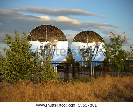 mirrored parabolic dish solar reflectors with trees and cloudy sky - stock photo