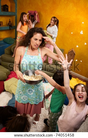 Misbehaving kids throwing popcorn with an unhappy babysitter - stock photo