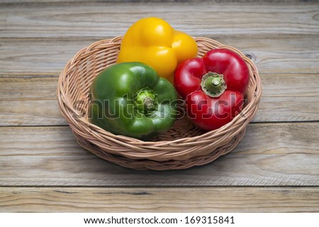 Miscellaneous colored peppers in a basket on a wooden table