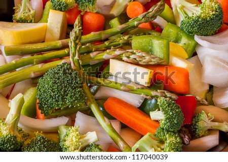 Miscellaneous fresh vegetables cut up in pieces ready for stir fry or saute. It includes carrots, broccoli, onions, asparagus, squash, and red and green pepper for healthy eating - stock photo