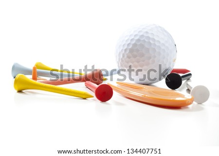 Miscellaneous parts used for playing golf: A ball, different colored tees, a pitch fork and a ball marker. Studio shot, shallow depth of field.