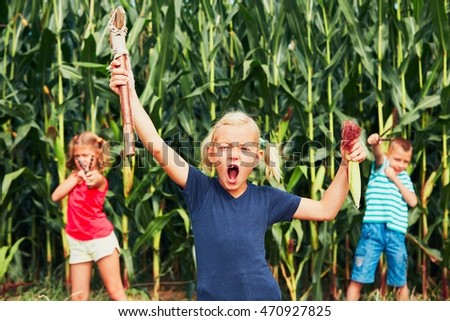 Mischievous girls and boy. Little girl is playing with her siblings in corn field.
