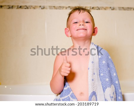 Mischievous little boy draped with a towel in his bath giving a cheeky broad grin as he makes a thumbs up gesture of approval - stock photo