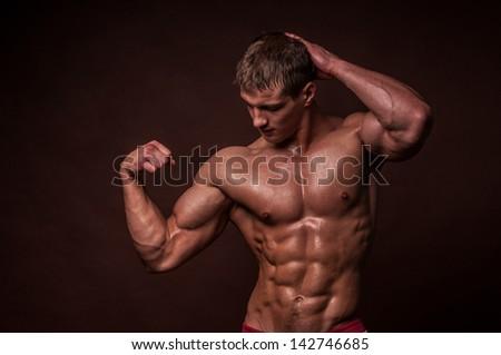 Miscled male model in studio - stock photo