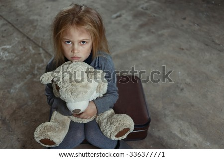 Miserable girl. Top view of little sad depressed girl holding her toy and begging for help while feeling unhappy - stock photo