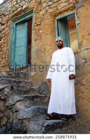 MISFA, OMAN - DEC 29 2007:Omani man wearing dishdash in Misfah,Oman.It's an ankle-length garment commonly worn in Arab countries. - stock photo