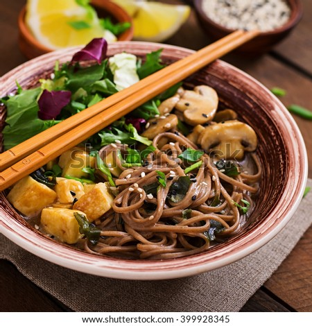 Miso and soba noodle soup with roasted tofu and mushrooms - stock photo