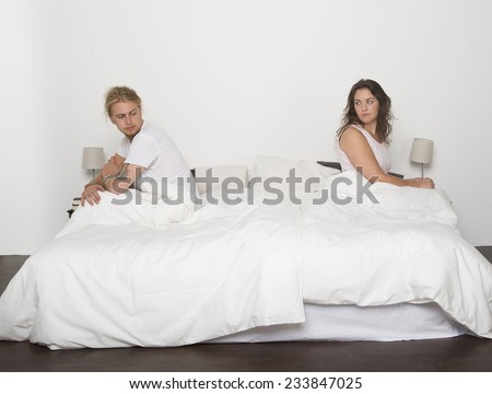 Mispleased couple in each part of the bed - stock photo