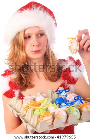 Miss Santa is holding a package of colourful easter eggs, one egg in her hand - sceptical look
