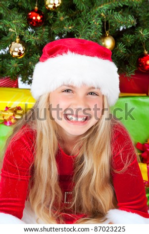 miss santa smiling, christmas tree in background - stock photo