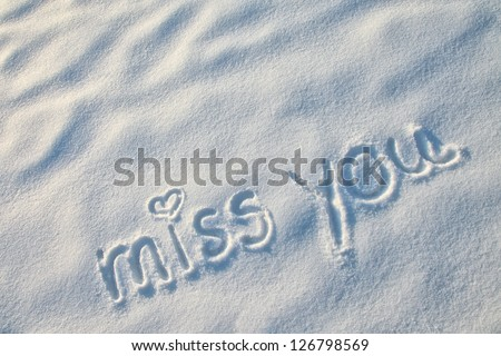 Miss you with heart sign writing on the snow. - stock photo
