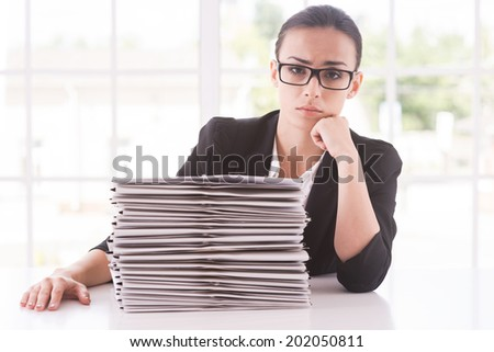 Missing deadlines. Depressed young woman in suit looking at camera and holding head on chin while sitting at the table with stack of documents laying on it - stock photo
